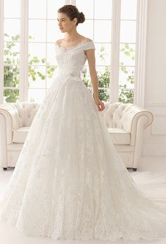 Brides: Aire Barcelona. Lace and tulle dress with beading and flower in a natural color.