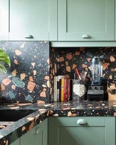 Im on love with color combination: a mint green cabinet with a darkened bold terrazzo back splash