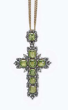 AN ANTIQUE PERIDOT AND DIAMOND PENDANT BROOCH  Designed as a rectangular-cut peridot cross, with a rose-cut diamond openwork foliate border, suspended by a similarly-set bail, to a twin gold ropework chain, mounted in silver-topped gold, the pendant circa 1880