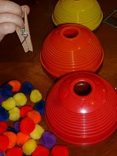 Great fine motor practice...use clothes pin to pick up pom poms and place through holes in nesting balls.