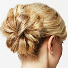 Take two invisible elastic bands and separate the hair into two ponytails, one above the other, in the back of your head. Once the ponytails are secured, take sections of each ponytail and, starting at the ends, roll them toward the head, pinning them in place with bobby pins. Roll the top ponytail first, then the bottom, leaving pieces closest to the middle for last