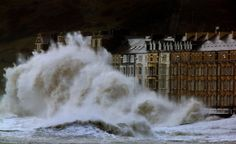 Waves crash against the Aberystwyth coastline, in Wales, as strong winds and high tides continue to blow in from the west on Jan. 6, 2014. (Dave Thompson/AP)
