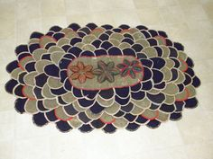 ANTIQUE PRIMITIVE OVAL RUG...PENNY STYLE...LATCH HOOK STARS..from old WOOL SUITS/The is a very old wool rug that has a penny rug feel. The center of the rug has colorful raised latch hook stars. The rows of ovals are made of old  wool suits of navy, black, dark brown, and herringbone. Each is outlined or edged in feedsack fabric. The backing is heavy rough cotton fabric.ebay sold 62.00