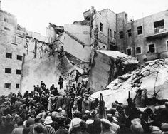 Jews surveying some of the damage caused by the Ben Yehuda bombing   The bombing was undertaken by Arab terrorists dressed up in British uniforms. 57 people died.