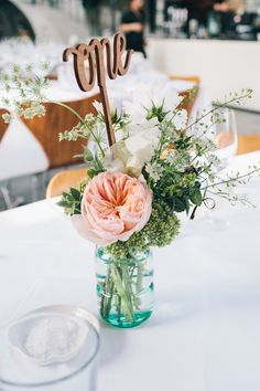 Glass Bottle Floral Wedding Centrepieces | Wooden Laser Cut Table number | Blush Pink Wedding Dress Tamsin by Catherine Deane For A Stylish London Wedding At 06 St Chads Place With Images From Robbins Photographic