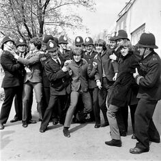 "The Beatles in the strong arm of the law while filming ""Help!"", outside The City Barge pub, Chiswick, London, 24 April 1965. Beatles members left to right: Paul McCartney, John Lennon, George Harrison, and Ringo Starr"