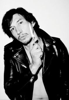 Adam Driver shirtless in a shiny black leather jacket holding a knife to his face
