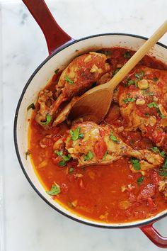 Cette recette de poulet à l'ail et tomates me vient de ma mère. C'est un plat savoureux et économique. Ce sont des morceaux de poulet cuits lentement et longuement dans une cocotte ou une grande poêle avec de l'ail et des tomates. Pas besoin de laisser mariner le poulet au préalable. Après cuisson, le poulet est très tendre, juteux et plein de saveurs.