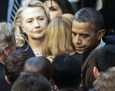 Secretary of State Hillary Clinton looks on as President Obama hugs a State Department employee following the assassination of 4 Americans in Libya.