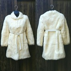 Vintage Genuine White Rabbit Fur Ivory Plush Coat Beautiful vtg coat is excellent vintage condition! 100% authentic rabbit fur. This coat is so soft, with rich creamy colors and a beautiful white satin lining. Picture 1 shows the coat with closed hooks and white belt. Picture 2 shows other styles the coat can be worn, belt is removable! Picture 3 shows the fur and satin lining up close. Picture 4 shoes the hook and eye closure feature. There are three hook and eyes on the coat, not visible…