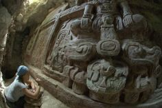 """Archaeologists have struck upon a """"once in a lifetime"""" find, an incredibly well-preserved 26-by-8-feet frieze buried beneath a temple in Holmul, a jungle-filled pre-Columbian research site in northeastern Guatemala, the BBC reports.  An archaeologist clearing debris away from an inscription on the newly discovered frieze. Photo: Francisco Estrada-Belli."""