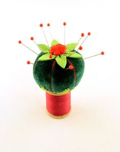 "❤ 2013 OOAK Janie Comito Velvet Earth Star Pin Cushion on Vintage Spool- A dainty sized & hand sewn from deep green velvet cupped in & capped with green ultra suede. The pin cushion, measuring 1 1/2"" wide by 1 3/8"" tall, is firmly filled with chopped wool felt, wool fiber & crushed garnet.  A charming vintage red glass flower button, is sewn on the center top for keeping your thimble.  The pin cushion is affixed to a small wooden Clarks brand spool still containing the original thread."