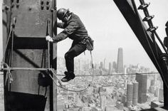 Construction worker atop the Sears Tower with Marina City and the Hancock in the background, 1973, Chicago