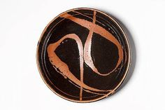 Shoji Hamada a large Dish with poured loops, mid 1960's stoneware, tenmoku with iron pours Diameter 14 1/2in. (37.5cm)
