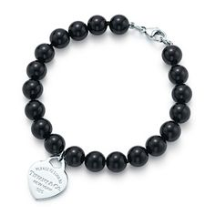 """Tiffany -Beads-web-may. 2013,USD 275, Inspired by a design from 1969, this celebrated collection bears an inscription that reminds one that there's no place like Tiffany. Small heart tag in sterling silver on a black onyx bead bracelet. 7.5"""" long. Beads, 8 mm."""