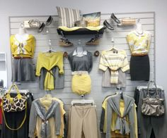 Visual Merchandiser, styling and still life designs The Claremore Goodwill® Store team matches brilliant shades of yellow with grays on a focal wall of women's fashions. Clothing Store Displays, Clothing Store Design, Visual Merchandising Fashion, Focal Wall, Boutique Ideas, Shades Of Yellow, Life Design, Showroom, Thrifting