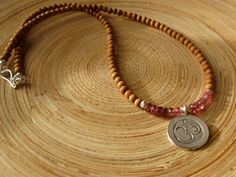 Fine silver om and pink tourmaline necklace with 108 sandalwood beads, $46.00