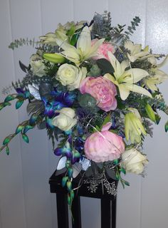 Peonies, lilies, roses and orchids make a statement in this cascade bouquet.
