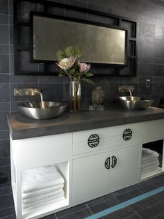 Clean lines, vessel sinks and Asian-style cabinet hardware give this gray-tiled bathroom a relaxing, Zen quality.