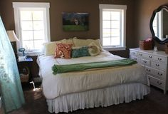 Brown walls, white bedding, white dresser, colorful accent pillows/throws