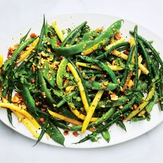 This is a high-summer throw-together of a sauté to make when there are lots of snap beans at the market. Mix colors and types for the full effect.