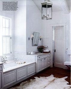 Tub positioned between sink vanities.