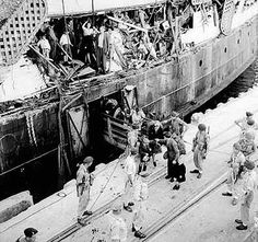 Exodus 1947 passengers disembark. Some stand in a hole torn open when a British war ship rammed the refugee ship. Later they were refused refuge and were forced to board the ship and were transported to Hamburg. They were beaten in Germany.