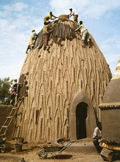 Cameroon - Maintenance being done on a musgum clay house.