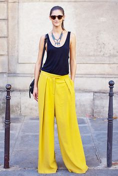Black tank top, bright yellow flared pants, and statement necklace