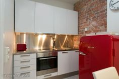 kitchen in white and steel shades with a brick wall and an adorable red Bosch fridge