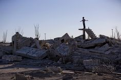 A young tourist stands on stairs protruding from the rubble of homes.