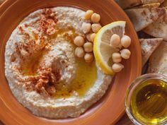 Hurry Up & Eat Hummus -  via AltonBrown-FoodNetwork - Ingredients:  2 - 15-ounce cans chickpeas, drained 2 cloves garlic, minced 1 1/2 tsp. kosher salt 1/3 c. tahini, stirred well 5 tbs fresh squeezed lemon juice 1/4 c.extra-virgin olive oil, + extra for service Optional Mediterranean powdered sumac &/or cumin to taste,