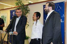 Ministro de Absorción Zeev Elkin (L) le habla a una reunión de los nuevos inmigrantes de la India, junto a su traductor (C) y director de Shavei Israel Rabino Michael Freund (R) el 18 de junio de 2015. (Laura Ben-David / Shavei Israel)