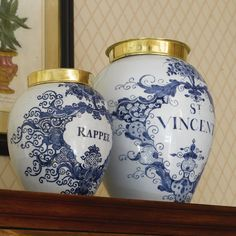 TWO DUTCH DELFT BLUE AND WHITE TOBACCO JARS 18TH CENTURY the larger inscribed St. Vincent, the smaller Rappee, with brass covers, painted factory marks. heights 13 and 9 in. 33 and 22.9 cm