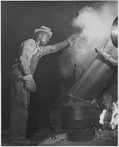 """Tennessee Valley Authority, Dams in Alabama, """"Muscle Shoals,"""" A Negro worker tending an electric phosphate smelting furnace which is producing elemental phosphorus at a TVA chemical plant in the Muscle Shoals area. Photo by Palmer. June, 1942"""
