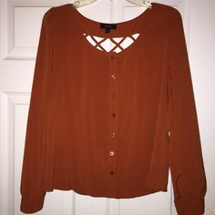 Burnt orange long sleeve cut out top Burnt orange long sleeve cut out top. Stretchy material very comfy light weight. Cute detail on back Tops Blouses