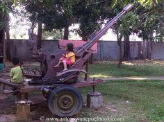 Girl sitting on an artillery, War museum, Siem Reap, Cambodia. www.antonswanepoelbooks.com