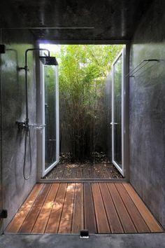 Douche ouverte sur un patio. Lame de bois, tadelakt, paroi de verre et bambou.