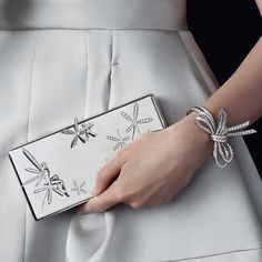 Inspired by Charles Arpels' American friend Florence Jay Gould, the Minaudière™ precious case pays homage to the essence of femininity. Caresse d'Eole Fairy Minaudière™ and Nœud Bracelet. #HighJewelry