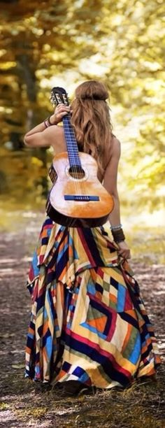 Boho - Hiking in a maxi dress with a guitar slung over her shoulders -