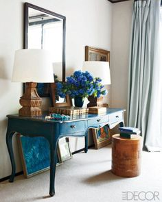 Wooden accents with a warm, orange undertone add a fresh touch to a cerulean table. White walls and curtains in a lighter blue keep the ornate corner from looking too fussy.