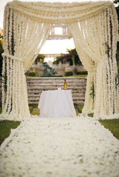 Canopy of hanging flower garlands and a chandelier in the center..