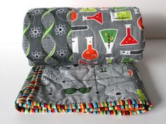 This adorable, unique baby quilt is completed and ready to ship to you! It features a fun, science theme with images of the periodic table, atoms, strands of DNA, mathematical formulas, bow ties, beakers, and more! The color palette is a mix of gray, green, and orange . It is finished off with a fun, striped edging. It would be a wonderful addition to a science-themed nursery and would make a wonderful gift for your nerdy best friend or little baby Einstein.  What makes this item great: ♥ It…