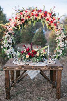 sweetheart table with giant wreath backdrop