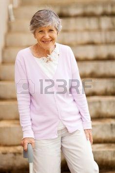 heureux debout vieille dame par un escalier de canne Banque d'images