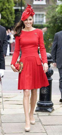 "Kate Middleton wearing ""a little red dress"" by Alexander McQueen. Pleated knee-length skirt, long sleeves, gentle ""boat"" neckline"