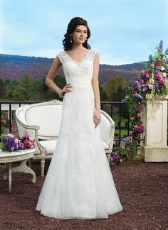 Sincerity wedding dress style 3813 Embroidered beaded lace slim A-line gown with a satin pleated cummerbund  at the natural waist and scattered lace appliques on the skirt. The  gown is finished with a key-hole back and tulle covered buttons to the  end of the semi-chapel length train.