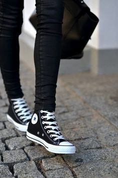 Black skinnies with black high-top Converse.