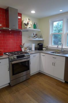 Design Craft Eaton  gloss white thermofoil cabinets with grey and red backsplash tile