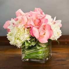 WHITE HYDRANGEA AND PINK ROSES WITH CYMBIDIUM ORCHIDS IN A SQUARE GLASS VASE